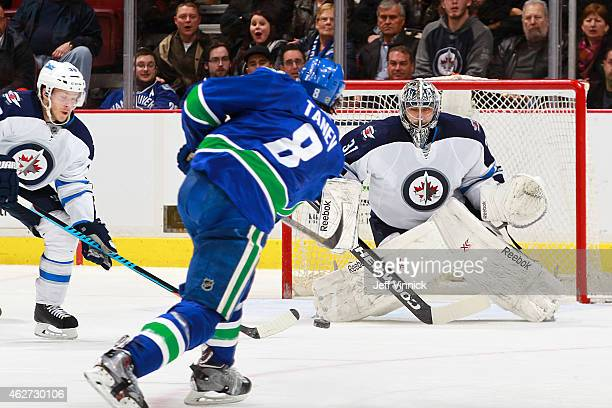 Christopher Tanev fires a shot at Ondrej Pavelec of the Winnipeg Jets during their NHL game at Rogers Arena February 3 2015 in Vancouver British...