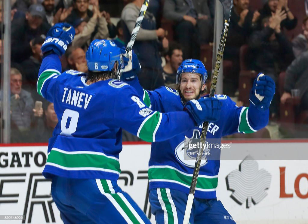 Christopher Tanev #8 is congratulated by teammate Michael Del Zotto #4 of the Vancouver Canucks after scoring during their NHL game against the Winnipeg Jets at Rogers Arena October 12, 2017 in Vancouver, British Columbia, Canada. The Winnipeg Jets won 4-2.