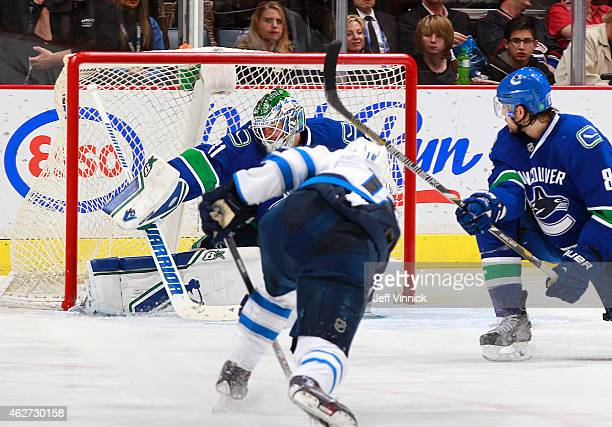 Christopher Tanev looks back as Bryan Little of the Winnipeg Jets beats Eddie Lack of the Vancouver Canucks for a goal during their NHL game at...