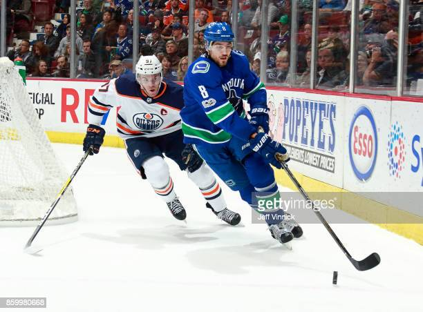 Christopher Tanev of the Vancouver Canucks and Connor McDavid of the Edmonton Oilers skate after a loose puck during their NHL game at Rogers Arena...