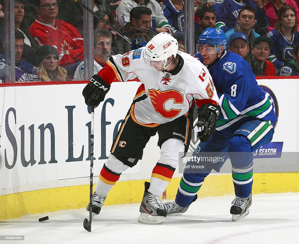 <a gi-track='captionPersonalityLinkClicked' href=/galleries/search?phrase=Christopher+Tanev&family=editorial&specificpeople=7228624 ng-click='$event.stopPropagation()'>Christopher Tanev</a> #8 of the Vancouver Canucks checks Maxwell Reinhart #59 of the Calgary Flames during their NHL game at Rogers Arena April 6, 2013 in Vancouver, British Columbia, Canada. Vancouver won 5-2