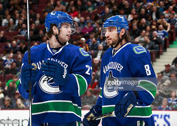 Christopher Tanev of the Vancouver Canucks listens to teammate Ben Hutton during their NHL game against the Minnesota Wild at Rogers Arena February...