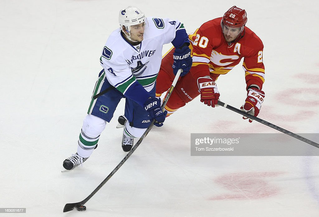 <a gi-track='captionPersonalityLinkClicked' href=/galleries/search?phrase=Christopher+Tanev&family=editorial&specificpeople=7228624 ng-click='$event.stopPropagation()'>Christopher Tanev</a> #8 of the Vancouver Canucks passes the puck during their NHL game as <a gi-track='captionPersonalityLinkClicked' href=/galleries/search?phrase=Curtis+Glencross&family=editorial&specificpeople=2190970 ng-click='$event.stopPropagation()'>Curtis Glencross</a> #20 of the Calgary Flames forechecks at the Scotiabank Saddledome on March 3, 2013 in Calgary, Alberta, Canada.