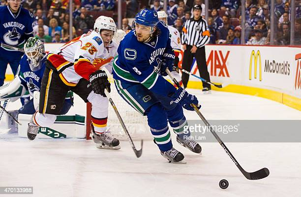 Christopher Tanev of the Vancouver Canucks picks up the loose puck while getting pressured by Sean Monahan of the Calgary Flames in Game One of the...