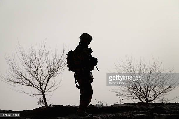 Christopher Tupper from Rincon Georgia with the US Army's 4th squadron 2d Cavalry Regiment patrols through a Kuchi a village on March 3 2014 near...