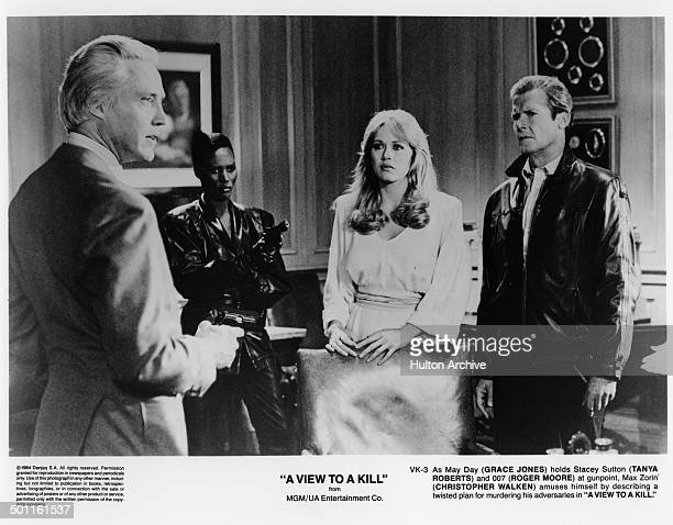 Christopher Walken holds at gunpoint Roger Moore and Tanya Roberts with the help of Grace Jones in a scene from the MGM/UA movie 'A View to a Kill'...