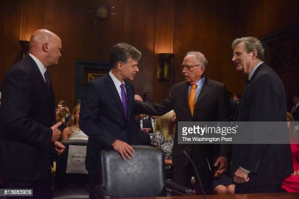 Christopher Wray 2nd from L greets Sam Nunn 2nd from R before Wray faces a confirmation hearing before the Senate Judiciary Committee on his...