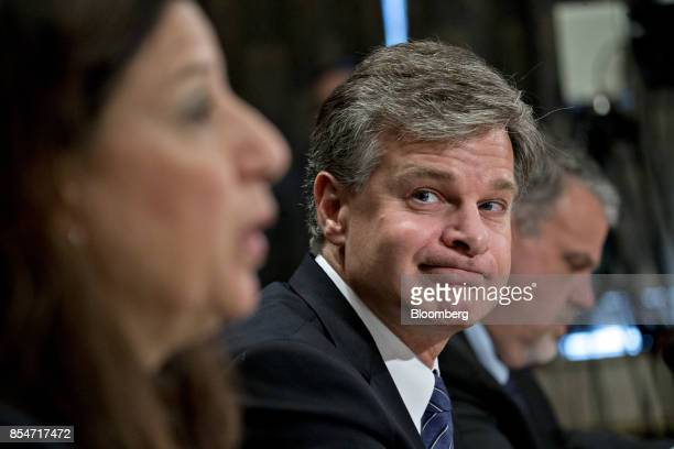 Christopher Wray director of the Federal Bureau of Investigation listens while Elaine Duke acting secretary of Homeland Security speaks left during a...