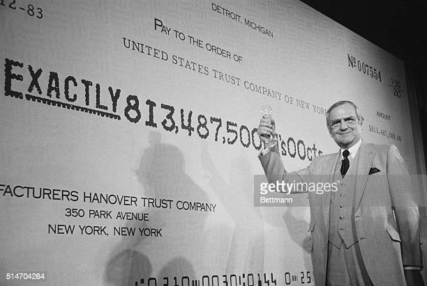Chrysler Corporation chairman Lee Iacocca raises his glass in a toast as he stands in front of a mock check for $813500 the final repayment of...