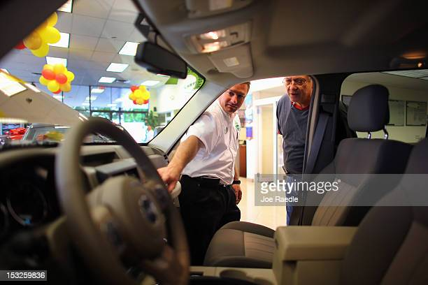 Chrysler sales consultant Doug Desloover shows a Jeep Liberty to Lewis Colon at the Hollywood Chrysler Jeep car dealership on October 2 2012 in...