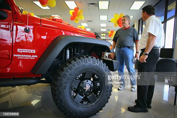 Chrysler sales consultant Doug Desloover shows a Jeep Wrangler to Lewis Colon at the Hollywood Chrysler Jeep car dealership on October 2 2012 in...