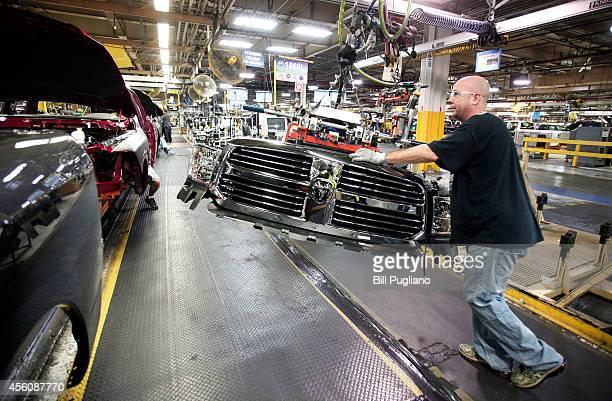 Chrysler worker installs a grill onto a Chrysler Ram 1500 truck on the assembly line at the Warren Truck Assembly Plant September 25 2014 in Warren...