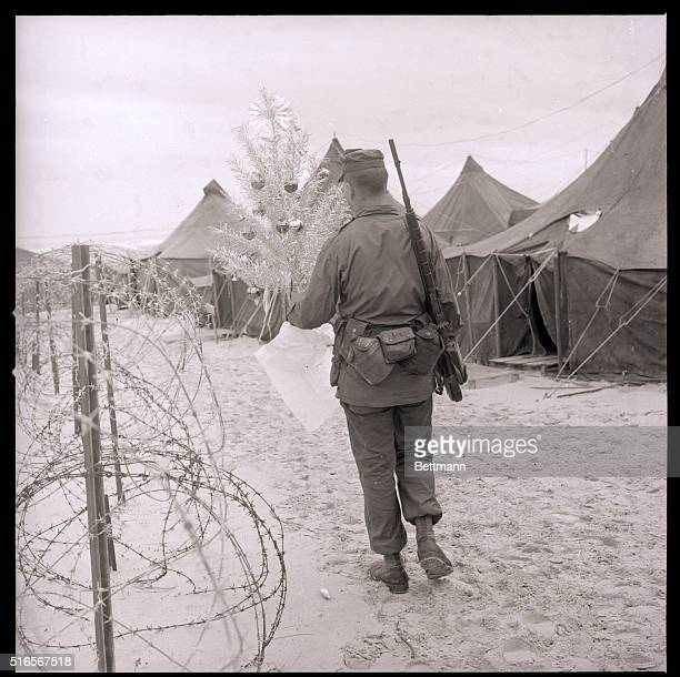 Chu Lai South Vietnam US Marine Pfc Richard Plummer of Carthage MO carries a decorated Christmas tree past the barbed wire barricade of the Marine...