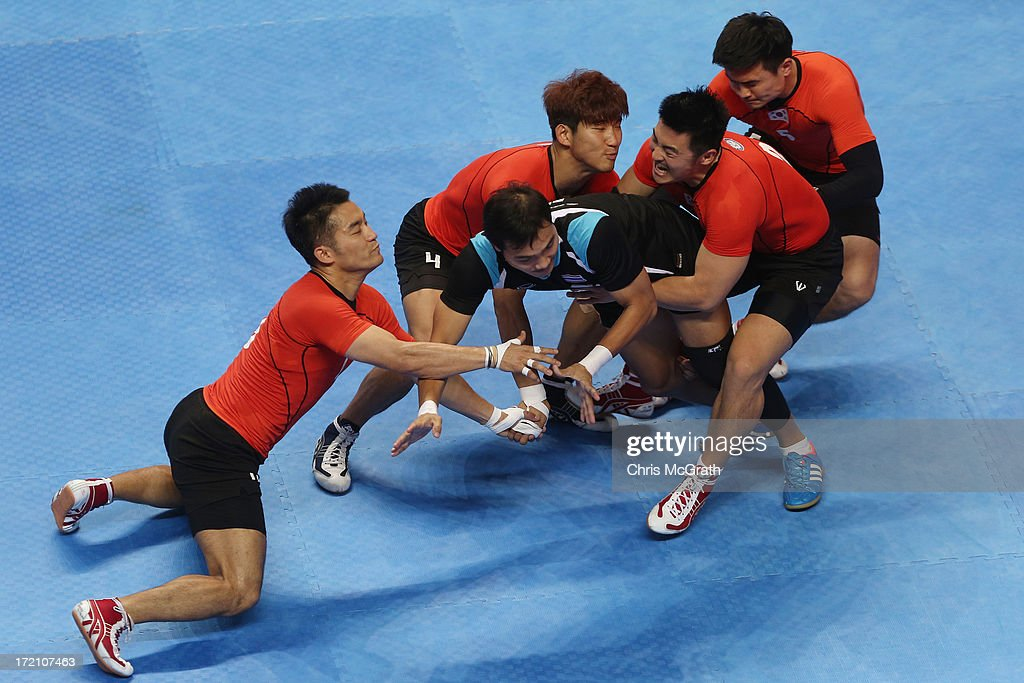 Chuaikoed Worawut #4 of Thailand is tackled by the Korea defence during the Kabaddi Men's Team Preliminary Match between Korea and Thailand at Ansan Sangnoksu Gymnasium on day four of the 4th Asian Indoor & Martial Arts Games on July 2, 2013 in Incheon, South Korea.