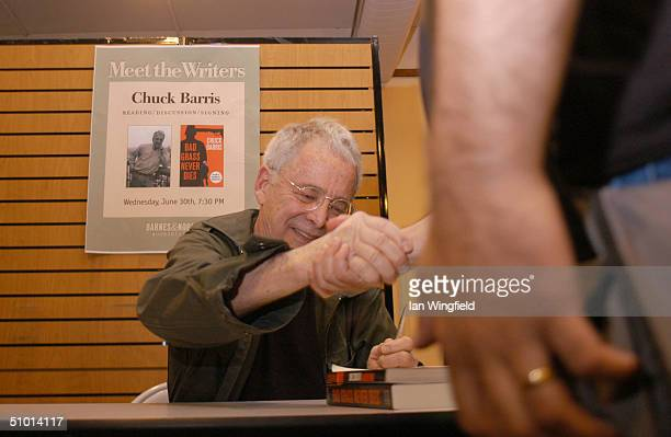 Chuck Barris shakes the hand of fan while signing copies of his newest book 'Bad Grass Never Dies' for fans during a signing June 30 2004 in New York...