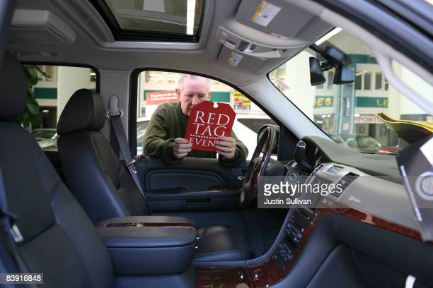 Chuck Garner looks at a special sale price tag for a brand new Cadillac Escalade Hybrid at Ellis Brooks Chevrolet December 4 2008 in San Francisco...