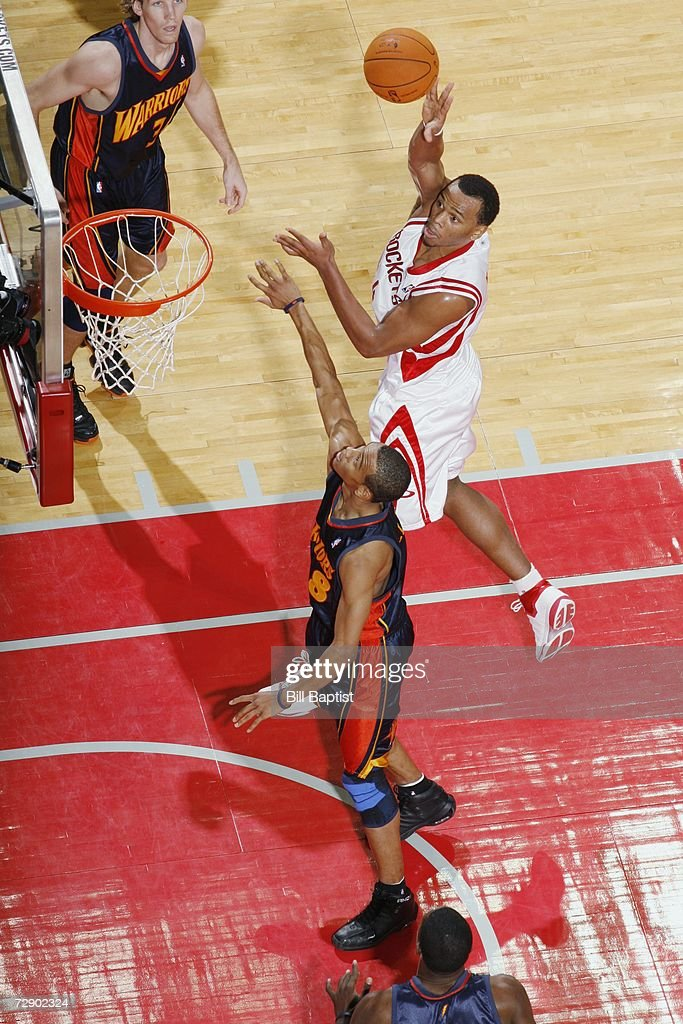 Chuck Hayes of the Houston Rockets shoots over Monta Ellis of the Golden State Warriors at the Toyota Center on December 5 2006 in Houston Texas The...