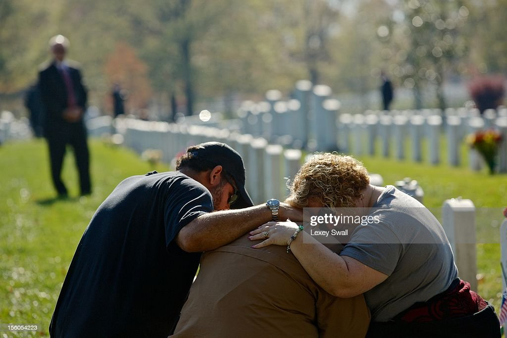 Chuck Jackson (L) and Kimberly Shrauger (R) comfort Kimberly's husband Lowell Shrauger as he visits the grave of his life-long friend, Staff Sgt. Jamie L. Huggins, on Veteran's Day at Arlington National Cemetery on November 11, 2012 in Arlington, Virginia. Numerous events are under across the country to honor the nation's current and former service members.
