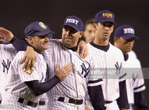 Chuck Knoblauch of the New York Yankees wearing a Port Authority hat and Luis Sojo wearing a New York Fire Department hat hug before their game...