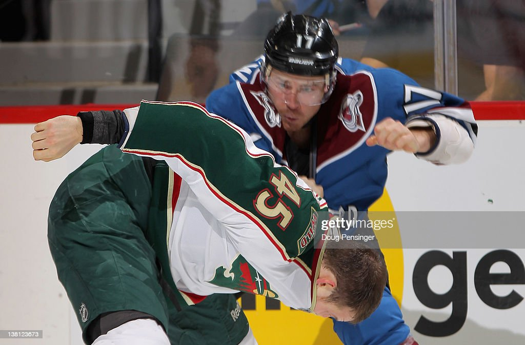 Chuck Kobasew of the Colorado Avalanche and Carson McMillan of the Minnesota Wild engage in a fight in the second period at the Pepsi Center on...