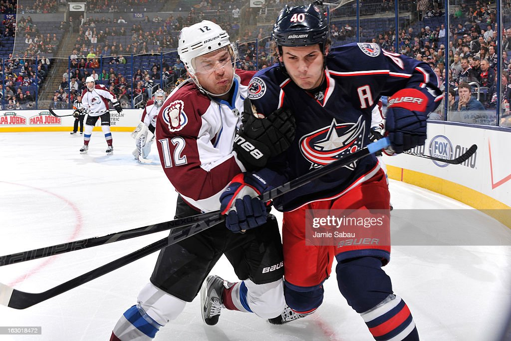 Chuck Kobasew of the Colorado Avalanche and Jared Boll of the Columbus Blue Jackets battle for position on a loose puck in the first period on March...