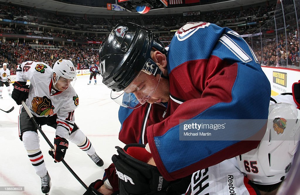 Chuck Kobasew of the Colorado Avalanche checks Andrew Shaw of the Chicago Blackhawks into the boards at the Pepsi Center on February 07 2012 in...