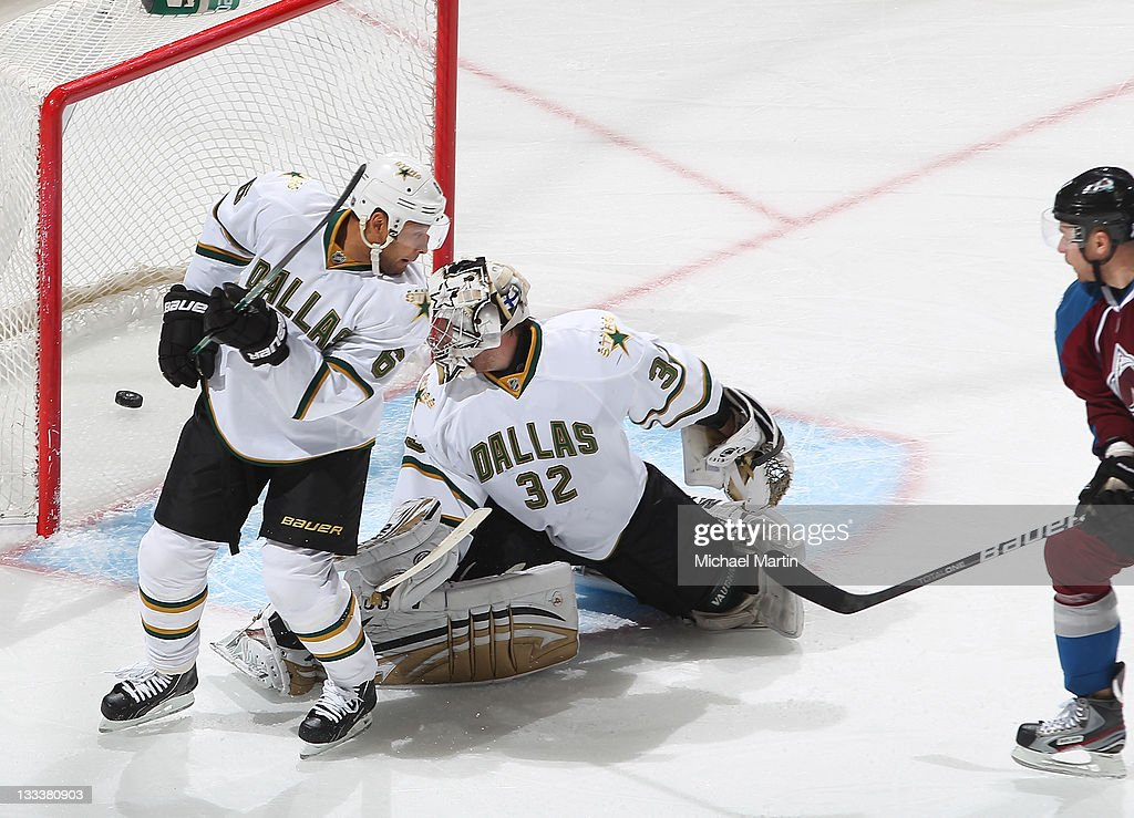 Chuck Kobasew of the Colorado Avalanche scores a goal against goaltender Kari Lehtonen and Trevor Daley of the Dallas Stars at the Pepsi Center on...