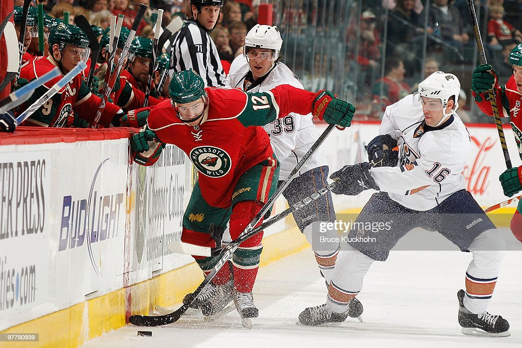 Chuck Kobasew of the Minnesota Wild fights for control of the puck with Chris Minard and Ryan Potulny of the Edmonton Oilers during the game at the...