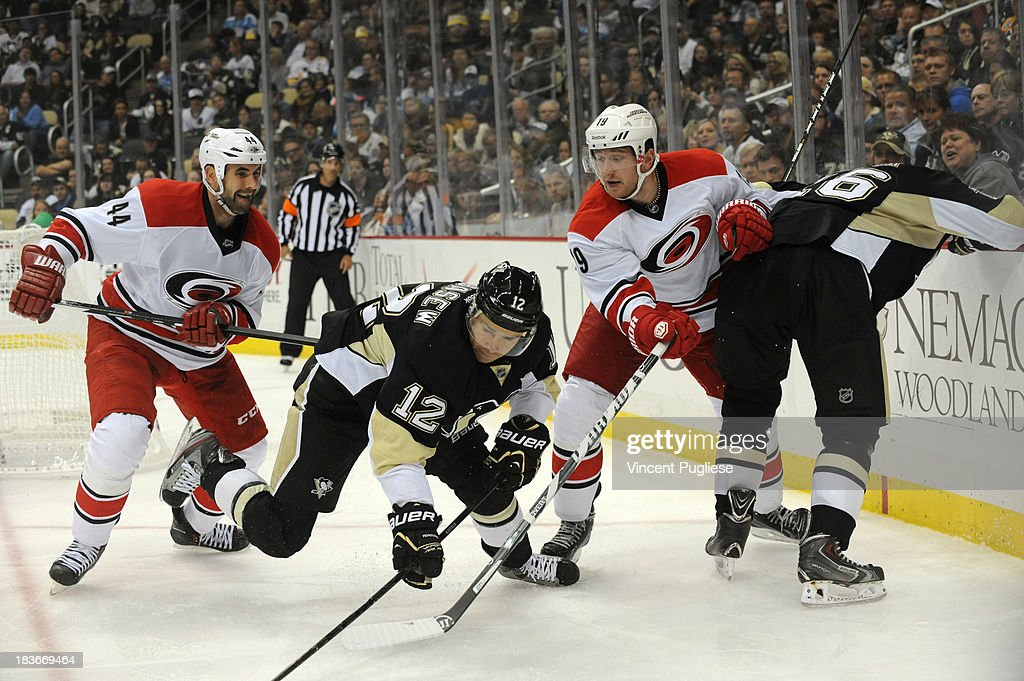 Chuck Kobasew #12 of the Pittsburgh Penguins battles past Jay Harrison #44 of the Carolina Hurricanes and Jiri Tlusty #19 of the Carolina Hurricanes during the third period on October 8, 2013 at the CONSOL Energy Center in Pittsburgh, Pennsylvania.