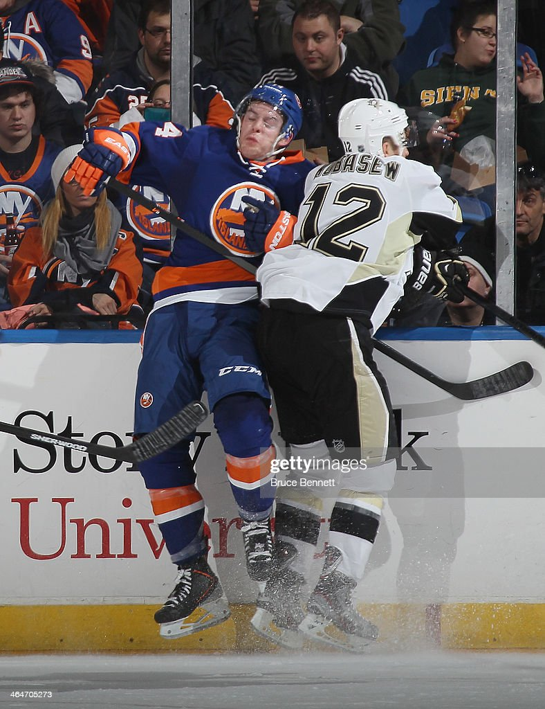 Chuck Kobasew of the Pittsburgh Penguins checks Calvin de Haan of the New York Islanders during the second period at Nassau Veterans Memorial...