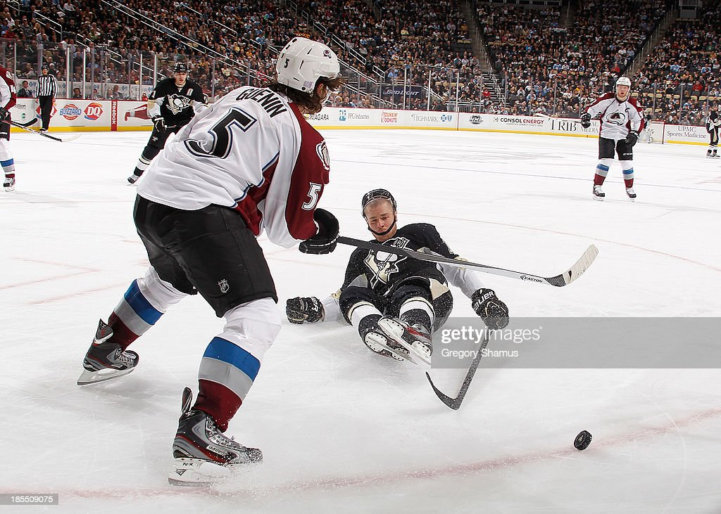 Chuck Kobasew of the Pittsburgh Penguins is knocked down by Nate Guenin of the Colorado Avalanche on October 21 2013 at Consol Energy Center in...