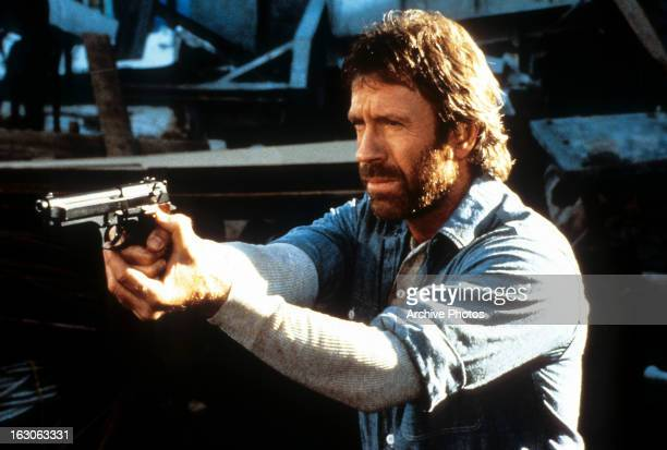 Chuck Norris points a gun in a scene from the film 'Hero And The Terror' 1988