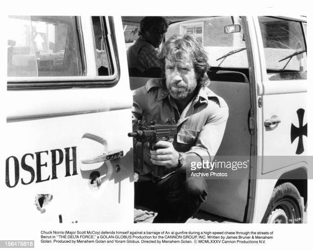 Chuck Norris shoots a gun in a scene from the film 'The Delta Force' 1986