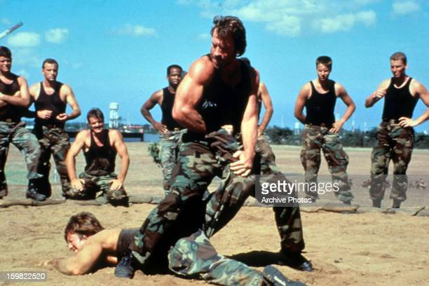 Chuck Norris wrestling with a military squad member in a scene from the film 'Delta Force 2' 1990