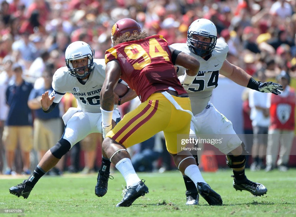 Chuckie Keeton #16 of the Utah State Aggies scrambles in front of Leonard Williams #94 of the USC Trojans and Jamie Markosian #54 during a 17-14 loss to the Trojans at the Los Angeles Memorial Coliseum on September 21, 2013 in Los Angeles, California.