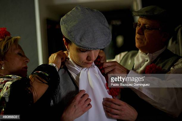 A 'Chulapa' adjust her handkerchief with the help of others at the 'Association of Rompe y Rasga' premises during the San Isidro festivities before...