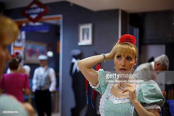 'Chulapa' Paloma Clemente prepares her hair at the 'Association of Rompe y Rasga' premises during the San Isidro festivities before making her way to...
