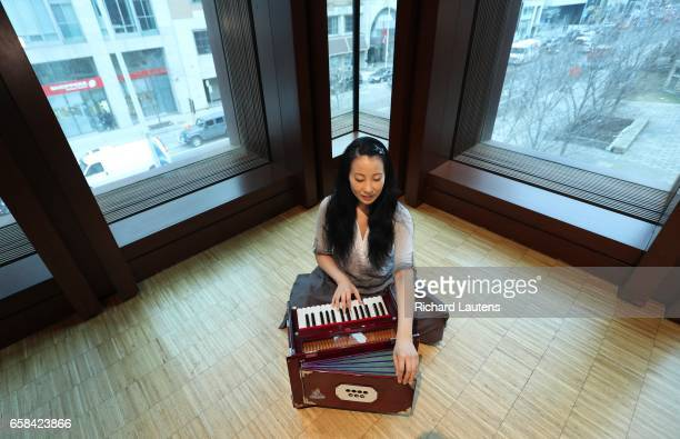 TORONTO ON MARCH 20 Chung chants the Shantih Mantra or Peace Invocation with her harmonium Yogi YuMee Chung demonstrates some yoga poses at the Royal...