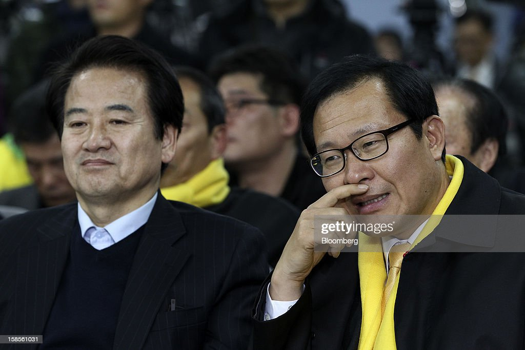Chung Dong Young, former presidential candidate of the United New Democratic Party, left, and an unidentified man react to television reports of the presidential election results at the party's headquarters in Seoul, South Korea, on Wednesday, Dec. 19, 2012. Park Geun Hye of the ruling New Frontier Party, was elected president of South Korea, defeating Moon Jae In from the main opposition Democratic United Party. Photographer: SeongJoon Cho/Bloomberg via Getty Images