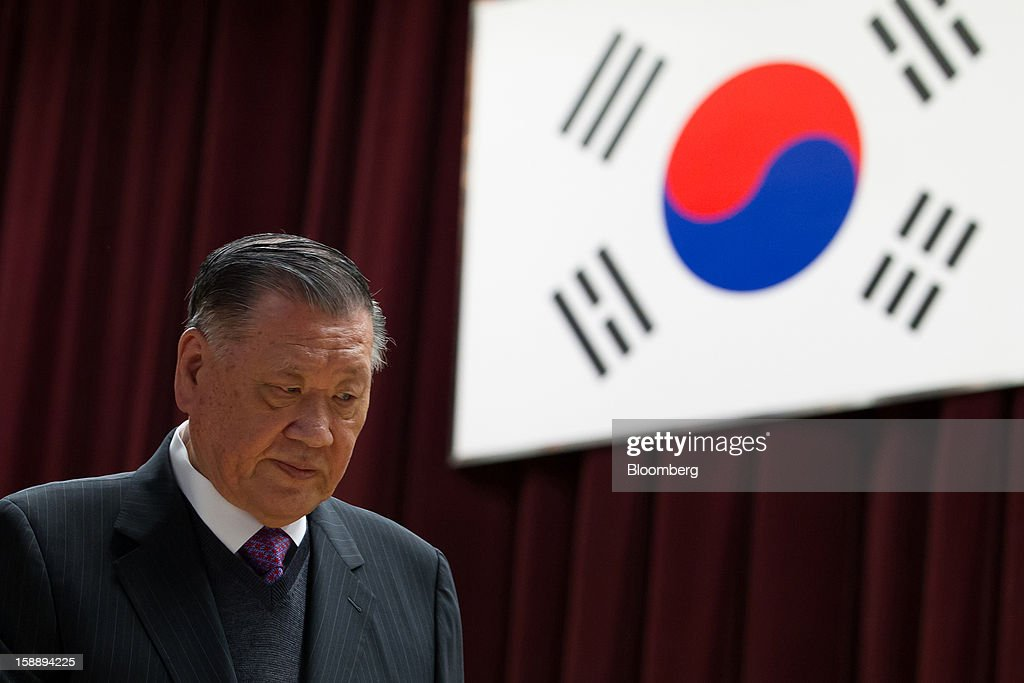 Chung Mong Koo, chairman of Hyundai Motor Co. and Kia Motors Corp., walks in front of South Korea's national flag during a new year company meeting in Seoul, South Korea, on Wednesday, Jan. 2, 2013. Hyundai Motor and smaller affiliate Kia Motors, South Korea's two largest automakers, forecast their slowest sales growth in seven years as a slowing global economy and strengthening won saps demand. Photographer: SeongJoon Cho/Bloomberg via Getty Images