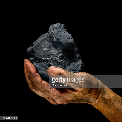 Chunk of coal in a dirty hand : Stock Photo