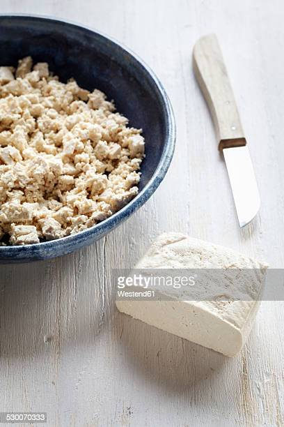 Chunk of tofu, bowl of chopped tofu and a kitchen knife