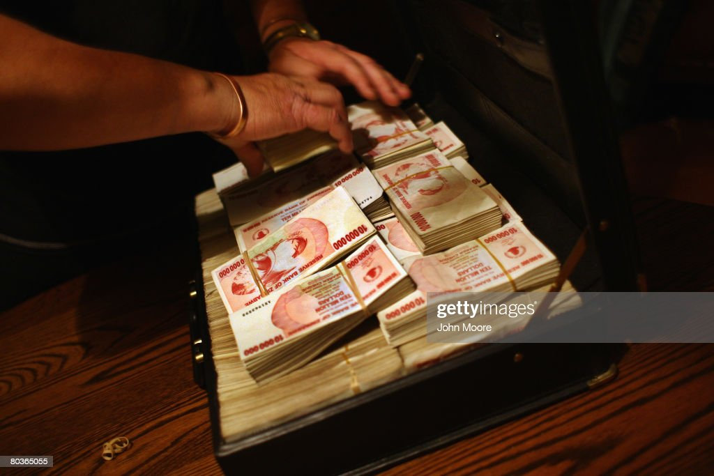 A church aid organizer packs $65 billion Zimbabwean dollars into a briefcase March 21 2008 in Bulawayo Zimbabwe He had received the foreign currency...