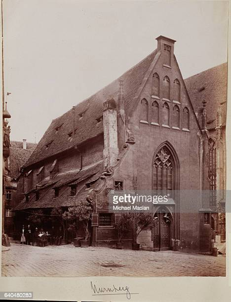 A church in Nurnberg Germany ca 1890 Several men sit at an outdoor table next to the church at the edge of a cobblestone square 'Bratwurstglocklein'...