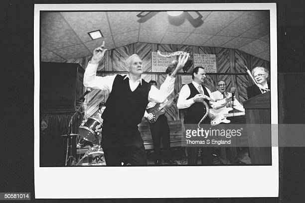 Church leader Dewey Chafin w Ray Christian handling timber rattlesnakes while trio of musicians play sing behind them during worship service at the...