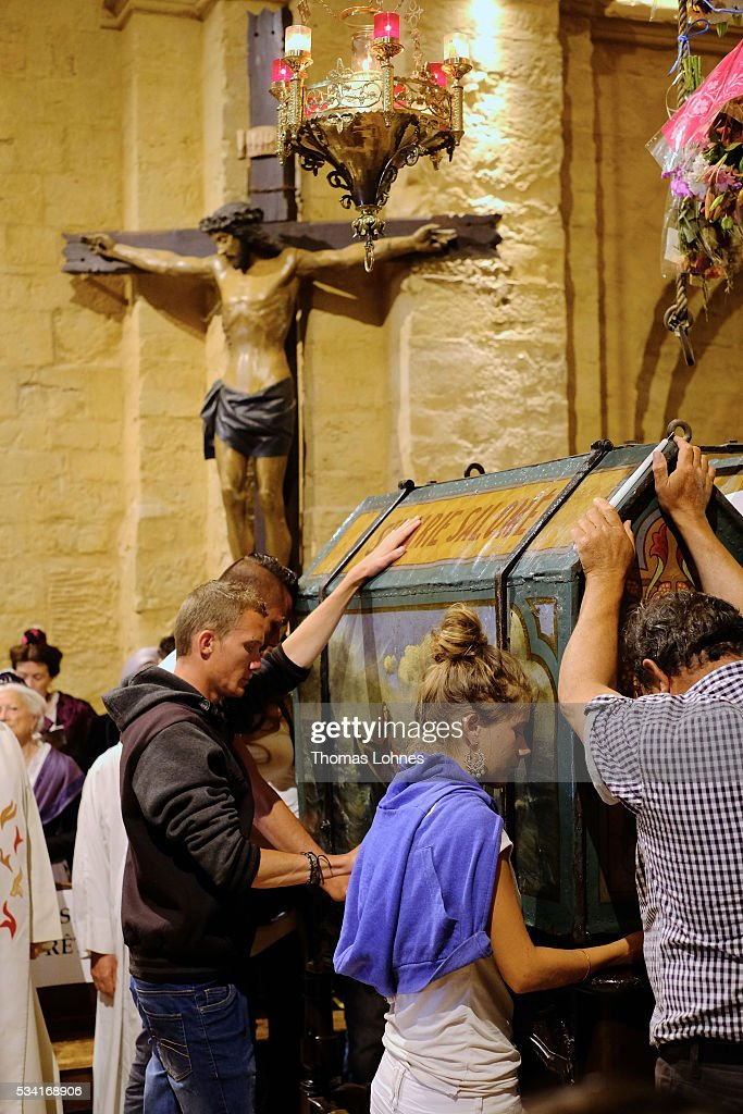 Church members pray at the casket with the reliquary of the local saintes Mary Salome and Mary Jacobe on May 25, 2016 in Saintes-Maries-de-la-Mer near Arles, France. Gypsies from all over Europe worship 'Sara the Black', their Saint and patroness, for one week. Sara's statue is situated in the crypt of the church.