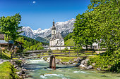 Scenic mountain landscape in the Bavarian Alps with famous Parish Church of St. Sebastian in the village of Ramsau in springtime, Nationalpark Berchtesgadener Land, Upper Bavaria, Germany.