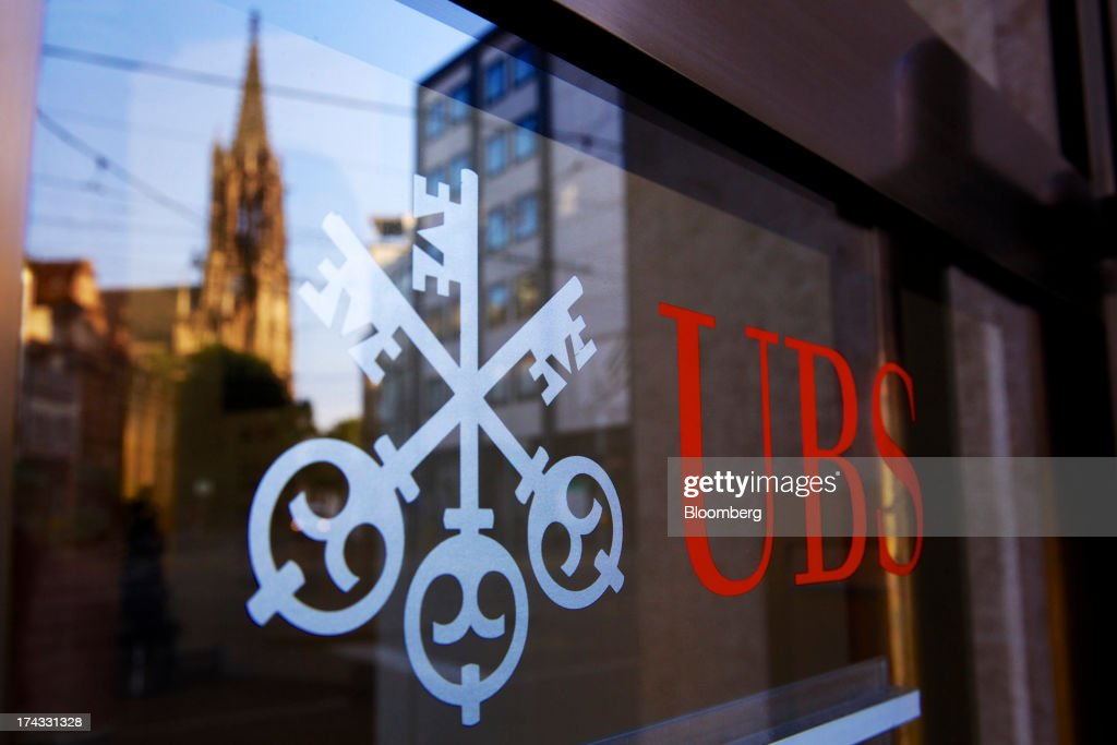 A church spire is seen reflected in the window of a UBS AG bank branch as the company's logo sits on display in Basel, Switzerland, on Tuesday, July 23, 2013. Europe's biggest banks, which more than doubled their highest-quality capital to $1 trillion since 2007 to meet tougher rules, may have further to go as regulators scrutinize how lenders judge the riskiness of their assets. Photographer: Gianluca Colla/Bloomberg via Getty Images