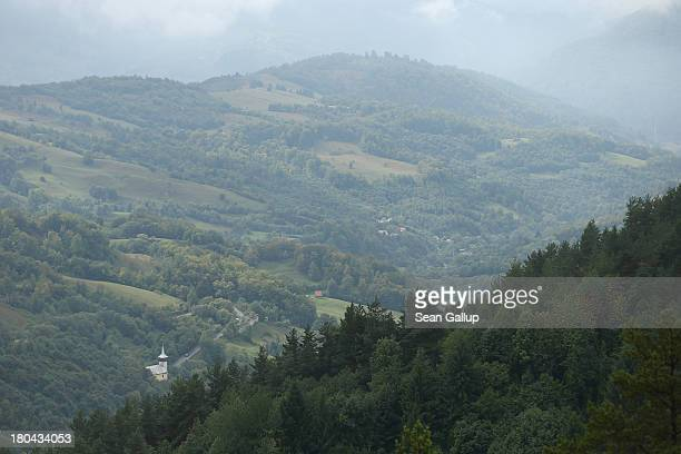 A church stands in the Corna valley as seen from Carnic mountain at the Rosia Montana gold mine site on September 12 2013 in Rosia Montana Romania...