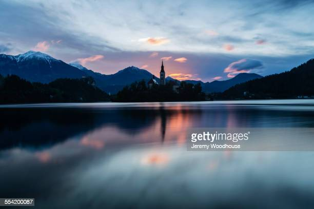Church tower and sunrise sky reflecting in still lake